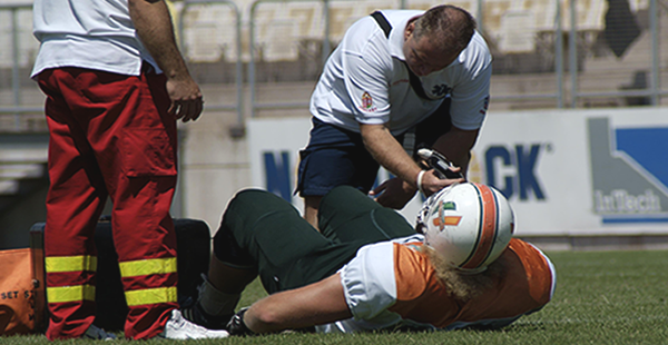 Medic Examining Football Player for Injury